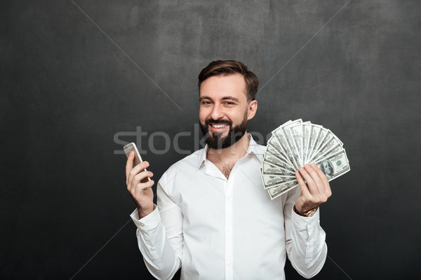 Portrait of cheerful man in white shirt winning lots of money do Stock photo © deandrobot