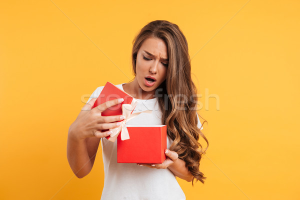 Portrait of an upset disappointed girl opening gift box Stock photo © deandrobot