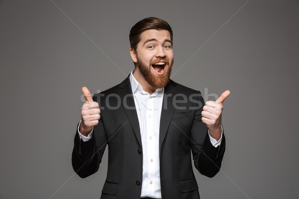 Portrait of a happy young businessman dressed in suit Stock photo © deandrobot