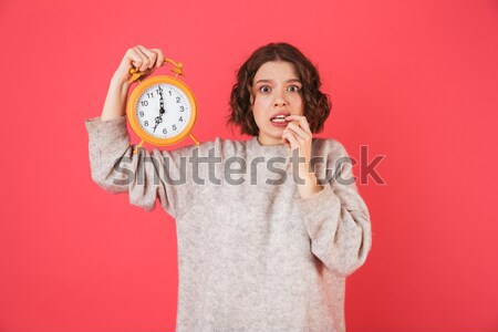 Happy woman holding alarm clock make thumbs up gesture. Stock photo © deandrobot