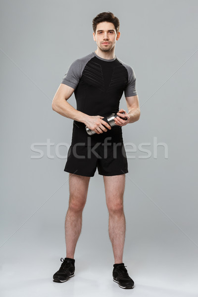 Handsome young sportsman holding bottle with water. Stock photo © deandrobot