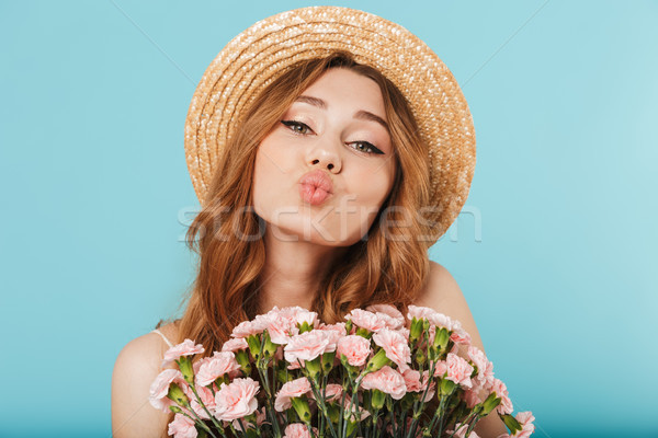 Cute caucasian woman holding flowers blowing kisses. Stock photo © deandrobot