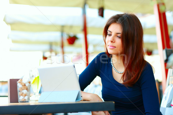 Elegant beautiful woman with tablet computer drinking coffee at cafe Stock photo © deandrobot