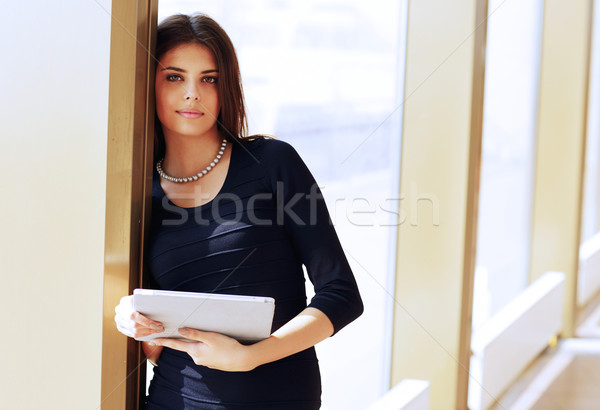Young beautiful female student standing at unviersity campus with tablet computer Stock photo © deandrobot