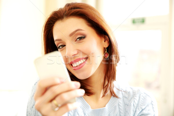 Smiling woman holding smartphone at home Stock photo © deandrobot