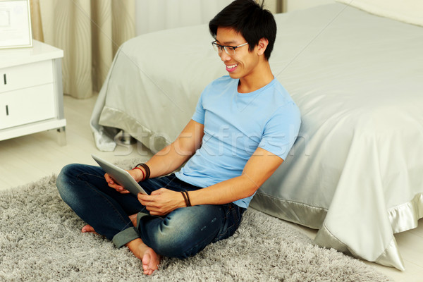 Smiling asian man sitting on the carpet with tablet computer Stock photo © deandrobot
