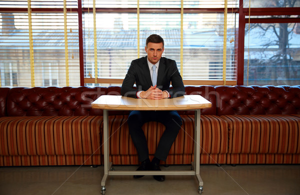 Confident businessman sitting at the table in office Stock photo © deandrobot