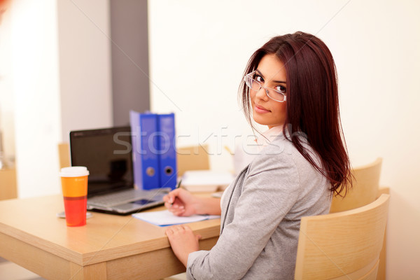 Stock photo: Young businesswoman sitting at desk and working. Smiling and looking back at camera