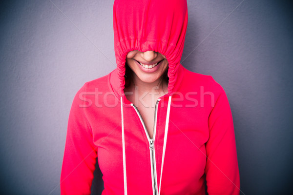 Portrait of a woman covering her eyes with hood Stock photo © deandrobot