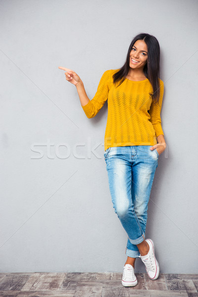 Pretty smiling woman showing finger left  Stock photo © deandrobot