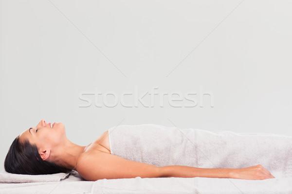 Happy woman lying on massage lounger Stock photo © deandrobot