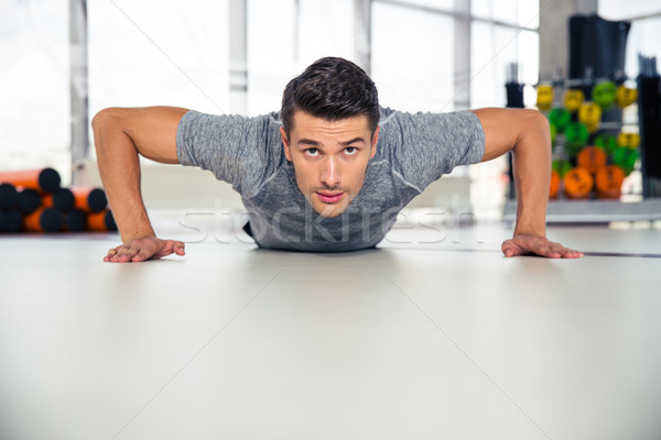 Handsome man doing push-ups in gym Stock photo © deandrobot