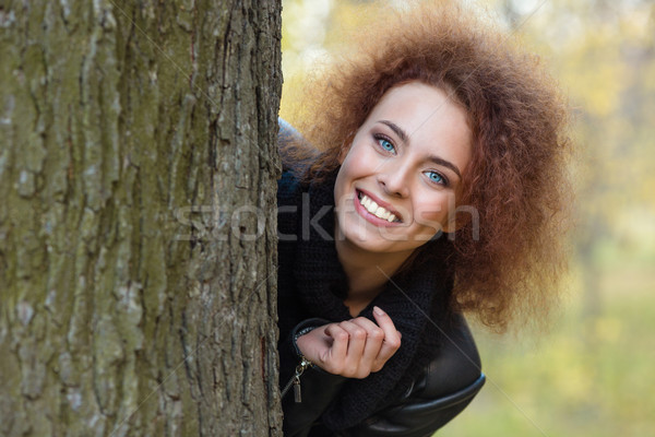 Woman with curly hair peeking out from behind a tree Stock photo © deandrobot
