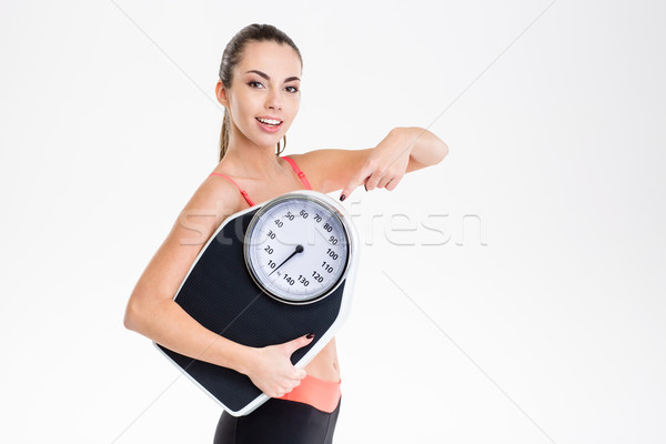 Pretty fitness girl holding weighing scale and pointing on it Stock photo © deandrobot