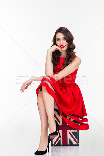 Happy attractive woman in red dress sitting on vintage suitcase Stock photo © deandrobot