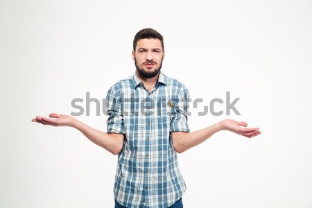 Confused annoyed young man with beard holding copyspace on palms Stock photo © deandrobot