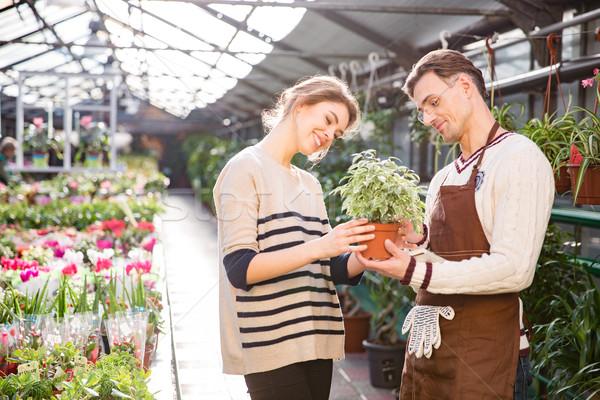 Cheerful woman with help of gardener choosing flowers in pot  Stock photo © deandrobot