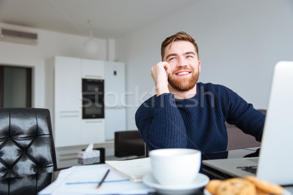 Smiling man talking on the phone at home Stock photo © deandrobot
