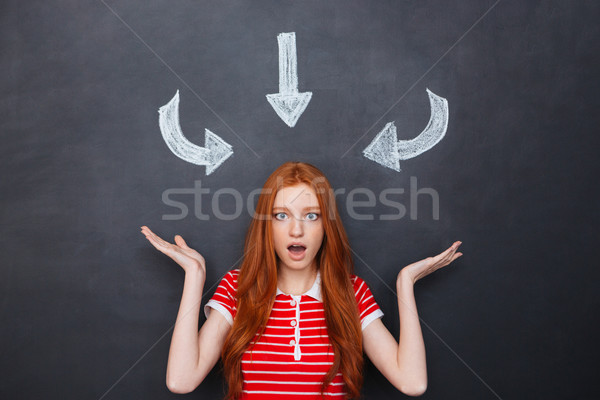 Wondered woman over blackboard with drawn arrows pointing on her Stock photo © deandrobot