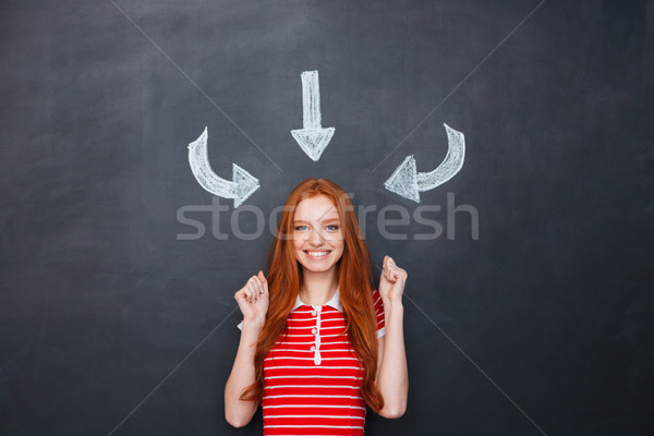 Excited happy woman enjoying attention and success over chalkboard background Stock photo © deandrobot