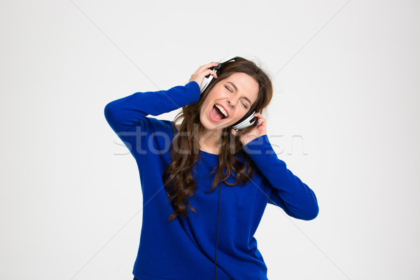 Happy pretty woman in headphones listening to music and singing Stock photo © deandrobot
