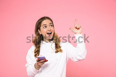 Amusing pretty woman holding her two long braids and shouting  Stock photo © deandrobot