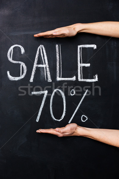 Two hands showing seventy percent sale drawn on blackboard  Stock photo © deandrobot