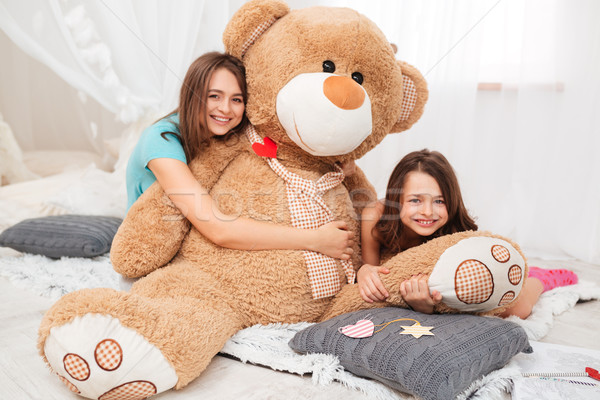 Two happy lovely sisters hugging plush bear in playroom Stock photo © deandrobot