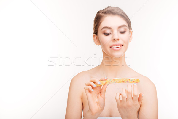 Beauty portrait of smiling young woman filing her nails Stock photo © deandrobot