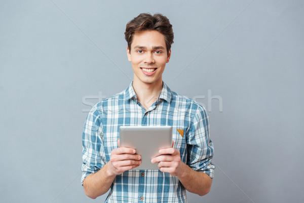 Mosolyog férfi tart táblagép lezser néz Stock fotó © deandrobot