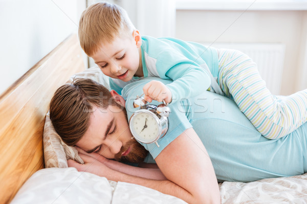 Little son holding alarm clock near sleeping father ear Stock photo © deandrobot