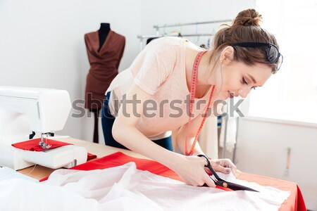 Serious woman seamstress thinking and reading notes in notebook Stock photo © deandrobot