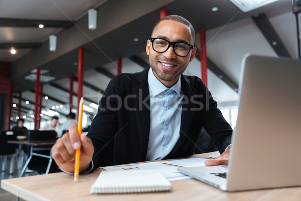 Businessman smiling at the working place Stock photo © deandrobot