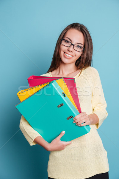 Smiling young girl holding folders Stock photo © deandrobot
