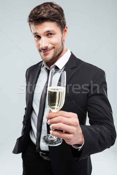 Smiling young businessman making cheers with glass of champagne Stock photo © deandrobot