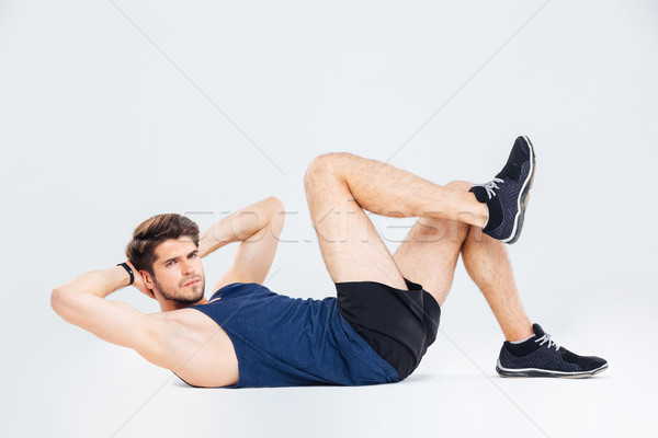 Handsome young man athlete working out and doing crunches Stock photo © deandrobot