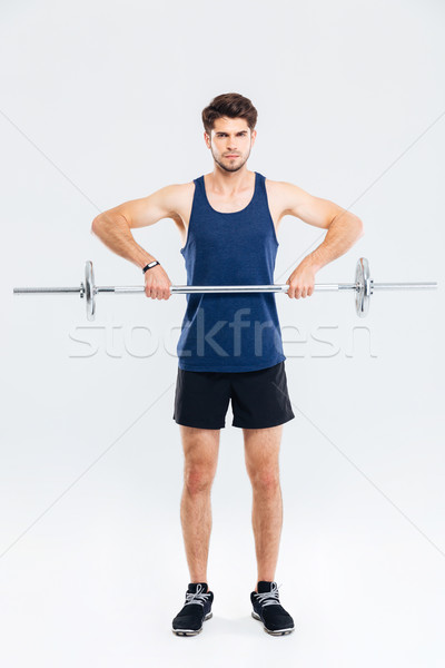 Full length of handsome young sportsman training and lifting barbell Stock photo © deandrobot