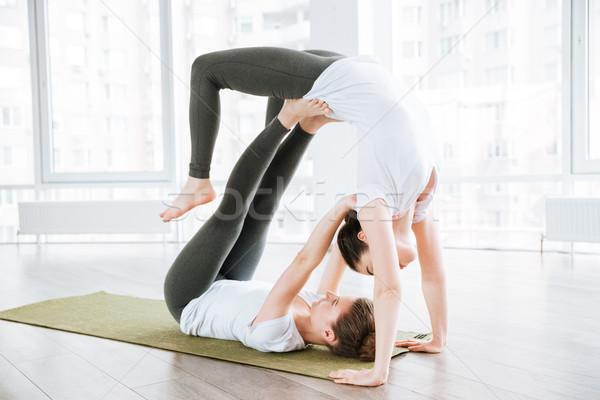 Kettő koncentrált fiatal nők akrobatikus jóga pozició Stock fotó © deandrobot