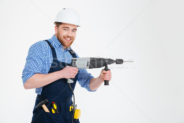 Happy attractive young builder smiling and using modern drill Stock photo © deandrobot