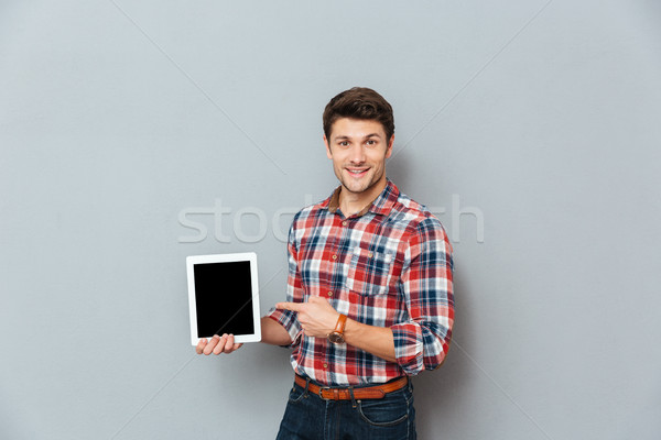 Cheerful man in checkered shirt pointing on blank screen tablet Stock photo © deandrobot
