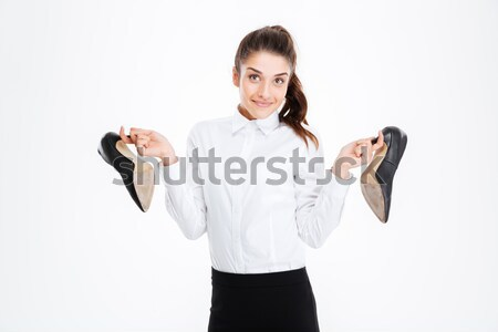 Happy cute young businesswoman holding high heels shoes Stock photo © deandrobot
