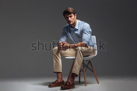 Serious handsome young man sitting and holding sunglasses Stock photo © deandrobot
