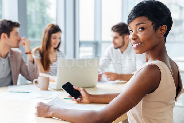 деловая женщина экране смартфон деловое совещание счастливым афроамериканец Сток-фото © deandrobot