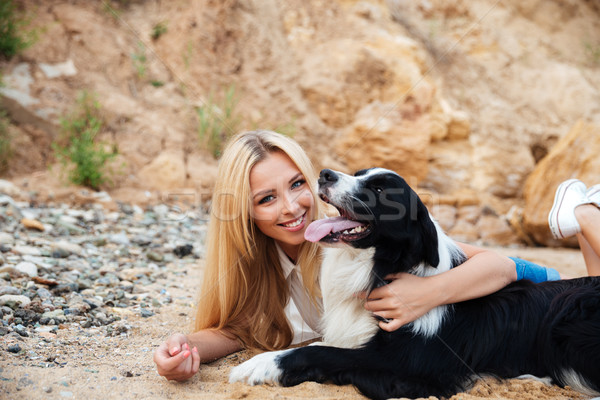 Smiling woman lying and hugging her dog on the beach Stock photo © deandrobot