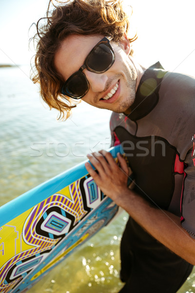 Young curly man in eyeglasses and swimsuit holding surf board Stock photo © deandrobot