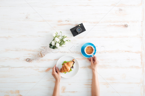 Hands of woman drinking coffee with croissant on wooden table Stock photo © deandrobot
