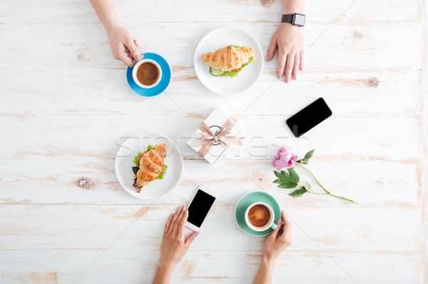 Hands of man and woman eating croissants with coffee Stock photo © deandrobot