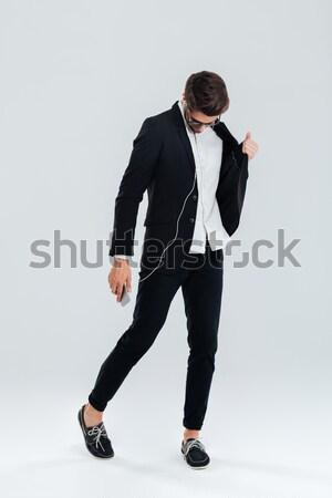 Işadamı siyah takım elbise dinleme müzik kulaklık dans Stok fotoğraf © deandrobot