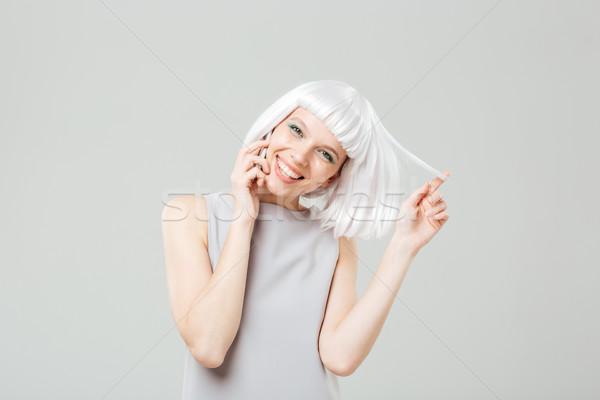 Derűs játékos nő szőke nő paróka beszél Stock fotó © deandrobot