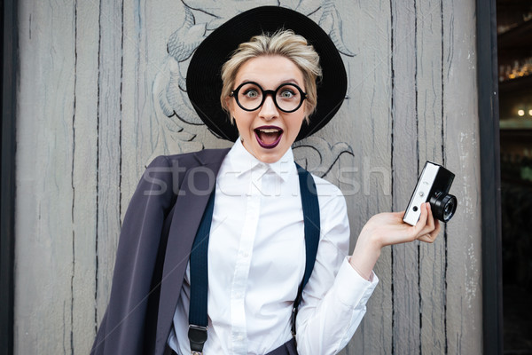 Happy surprised young woman photographer holding photo camera Stock photo © deandrobot